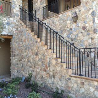 На фото: прямая лестница в стиле рустика с ступенями из травертина, подступенками из травертина и металлическими перилами