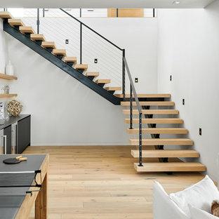 Foto de escalera suspendida, contemporánea, grande, sin contrahuella, con escalones de madera y barandilla de metal
