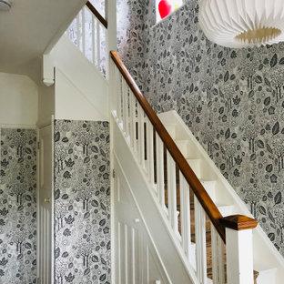 Стильный дизайн: угловая лестница среднего размера в скандинавском стиле с деревянными ступенями, деревянными подступенками, деревянными перилами и обоями на стенах - последний тренд