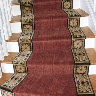 Ispirazione per una scala curva tradizionale di medie dimensioni con pedata in legno e alzata in legno verniciato