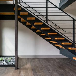 На фото: большая лестница на больцах в стиле модернизм с деревянными ступенями без подступенок