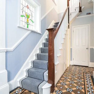 This is an example of a traditional carpeted l-shaped wood railing staircase in London with carpeted risers.