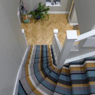 Imagen de escalera en L y papel pintado, contemporánea, de tamaño medio, con escalones enmoquetados, contrahuellas enmoquetadas, barandilla de madera y papel pintado