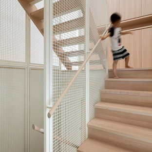 Photo of a scandinavian wood u-shaped staircase in Melbourne with wood risers.