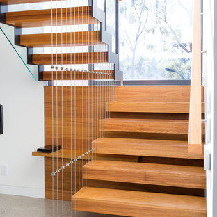 This is an example of a large contemporary wood floating staircase in Melbourne with open risers.