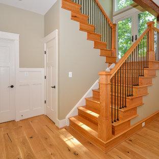 Ejemplo de escalera en U, de estilo americano, con escalones de madera y contrahuellas de madera