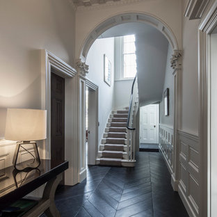 Example of a large classic painted floating staircase design in London with painted risers