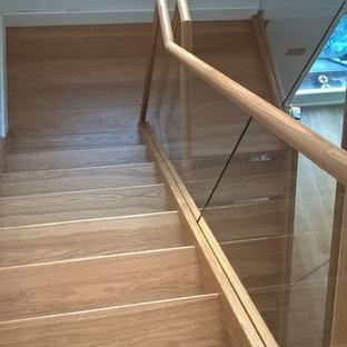 Imagen de escalera suspendida, actual, grande, con escalones de madera y contrahuellas de vidrio