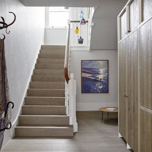ロンドンの広い木のラスティックスタイルのおしゃれな折り返し階段 (木の蹴込み板、木材の手すり) の写真
