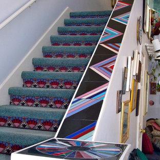 Imagen de escalera minimalista con escalones enmoquetados y contrahuellas con baldosas y/o azulejos