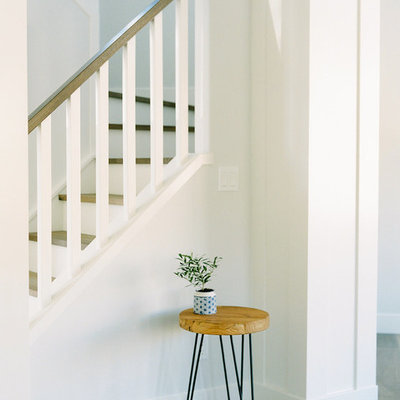 Staircase - mid-sized cottage wooden u-shaped wood railing staircase idea in Calgary with painted risers