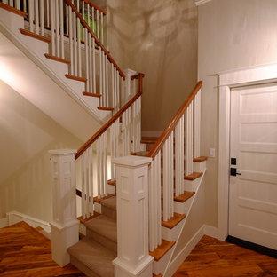 サクラメントの広いカーペット敷きのおしゃれな折り返し階段 (カーペット張りの蹴込み板、木材の手すり) の写真