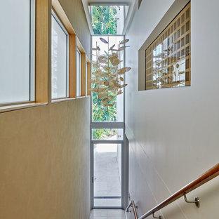 Immagine di una scala a rampa dritta minimal di medie dimensioni con parapetto in legno e pedata in pietra calcarea