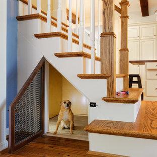 Imagen de escalera clásica con escalones de madera, barandilla de madera y contrahuellas de madera pintada