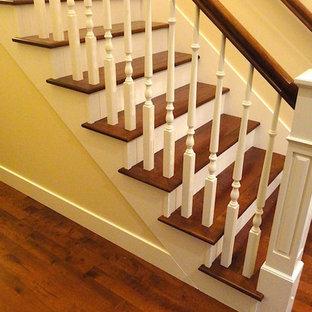 Foto de escalera en L, clásica, de tamaño medio, con escalones de madera, contrahuellas de madera y barandilla de madera
