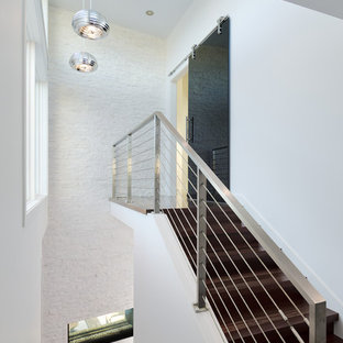 Design ideas for a contemporary wood wire cable railing staircase in Vancouver with wood risers.