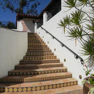 Новый формат декора квартиры: лестница в средиземноморском стиле с подступенками из плитки, ступенями из терракотовой плитки и металлическими перилами