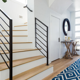 Inspiration for a transitional wooden curved metal railing staircase remodel in Los Angeles with wooden risers
