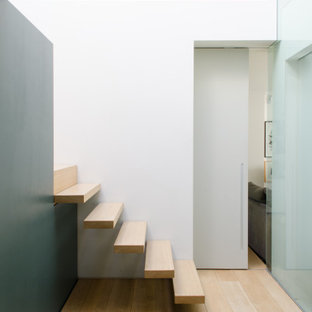 Design ideas for a contemporary wood floating staircase in London with wood risers.