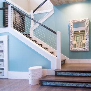 ジャクソンビルの広い木のトロピカルスタイルのおしゃれな折り返し階段 (タイルの蹴込み板、ワイヤーの手すり) の写真
