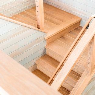 ポートランド(メイン)の中くらいの木のビーチスタイルのおしゃれな折り返し階段 (木の蹴込み板、ワイヤーの手すり) の写真