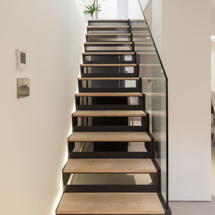 Inspiration for a contemporary wood straight glass railing staircase in London with open risers.