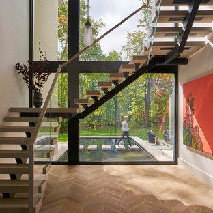 """Immagine di una scala a """"L"""" contemporanea con pedata in legno, nessuna alzata e parapetto in materiali misti"""