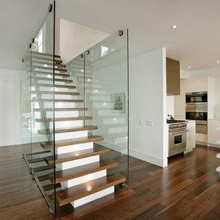 Immagine di una scala a rampa dritta minimalista di medie dimensioni con pedata in legno e alzata in legno verniciato