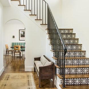 На фото: угловые лестницы в средиземноморском стиле с деревянными ступенями, подступенками из плитки и металлическими перилами