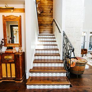 オースティンのテラコッタのカントリー風おしゃれな折り返し階段 (木の蹴込み板、金属の手すり) の写真