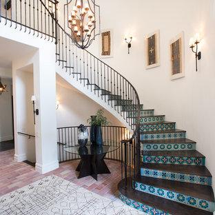Modelo de escalera curva, mediterránea, con escalones de madera, contrahuellas con baldosas y/o azulejos y barandilla de metal