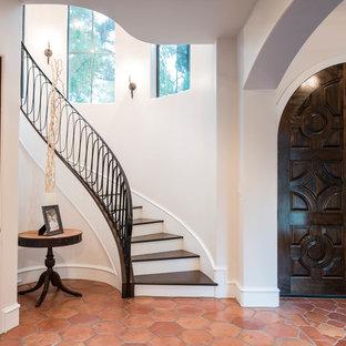 Ejemplo de escalera curva, mediterránea, de tamaño medio, con escalones de madera, contrahuellas de madera pintada y barandilla de metal