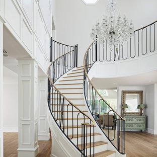 Ejemplo de escalera curva, clásica, extra grande, con escalones de madera, barandilla de metal y contrahuellas de madera pintada