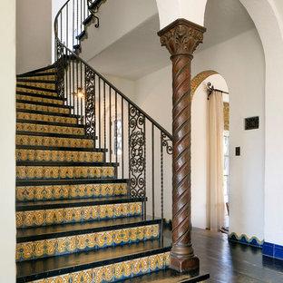Ejemplo de escalera curva, mediterránea, extra grande, con escalones de madera pintada y contrahuellas con baldosas y/o azulejos