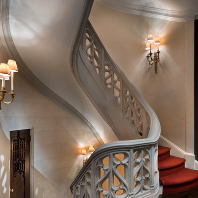 Example of a huge classic carpeted spiral staircase design in New York with wooden risers