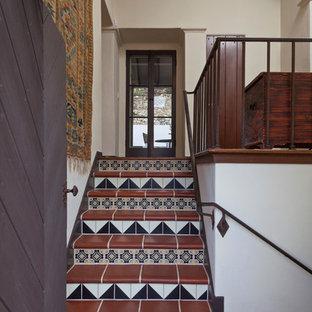 Réalisation d'un escalier méditerranéen avec des contremarches en carrelage, des marches en terre cuite et un garde-corps en métal.