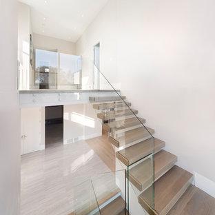 Modelo de escalera suspendida, minimalista, grande, con escalones de madera, contrahuellas de madera y barandilla de vidrio