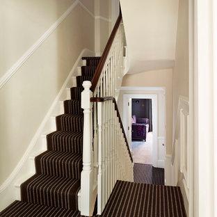 На фото: большая угловая лестница в викторианском стиле с ступенями с ковровым покрытием и ковровыми подступенками с