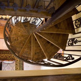 Immagine di una scala a chiocciola mediterranea di medie dimensioni con pedata in legno, nessuna alzata e parapetto in metallo