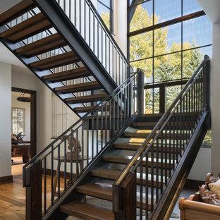 Foto de escalera en U, rústica, sin contrahuella, con escalones de madera y barandilla de metal