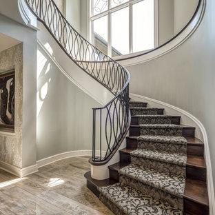 На фото: огромная изогнутая лестница в стиле современная классика с ступенями с ковровым покрытием, ковровыми подступенками и металлическими перилами с