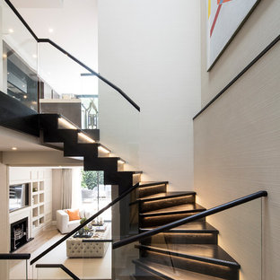 This is an example of a medium sized contemporary wood u-shaped glass railing staircase in London with wood risers.