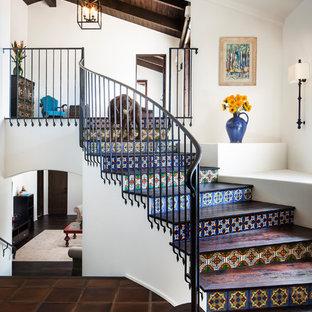 サンタバーバラの中サイズの木の地中海スタイルのおしゃれなサーキュラー階段 (タイルの蹴込み板、金属の手すり) の写真
