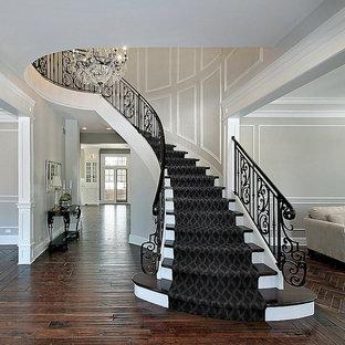 Diseño de escalera curva, tradicional, grande, con escalones enmoquetados, contrahuellas enmoquetadas y barandilla de metal