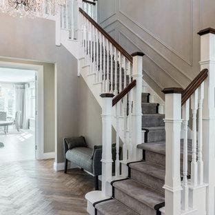 Ejemplo de escalera en L, clásica, extra grande, con contrahuellas de madera pintada, barandilla de madera y escalones de madera pintada
