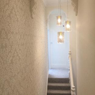 Ejemplo de escalera recta y papel pintado, moderna, de tamaño medio, con escalones enmoquetados, contrahuellas enmoquetadas, barandilla de madera y papel pintado