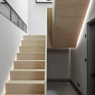 Inspiration for a medium sized contemporary wood u-shaped wood railing staircase in London with wood risers.