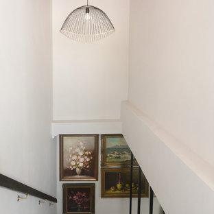 Diseño de escalera en L, de tamaño medio, con escalones de acrílico y barandilla de metal