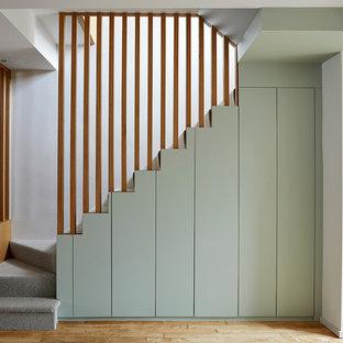 Esempio di una scala minimalista di medie dimensioni con pedata in moquette, alzata in moquette e parapetto in legno