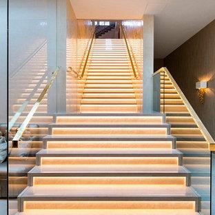 ロンドンの巨大なガラスのコンテンポラリースタイルのおしゃれな直階段 (ガラスの蹴込み板) の写真